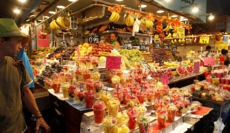 1149010_tourists-look-at-a-fruit-juice-stand-in-the-la-boqueria-market-in-barcelona